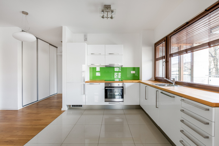 White, open kitchen with window, green backsplash and wooden countertop Stock Photo