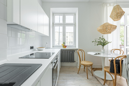 White kitchen in scandinavian style with round table and wooden chairs Standard-Bild