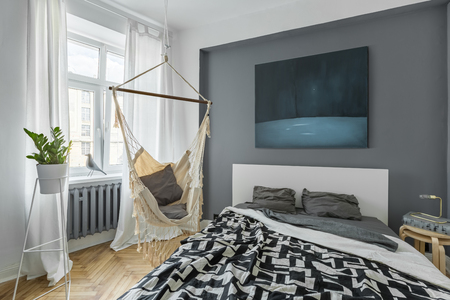Nordic bedroom with double bed, hammock and modern painting
