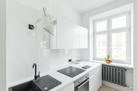 Kitchen with white tiling, simple furniture and window 版權商用圖片 - 81549159