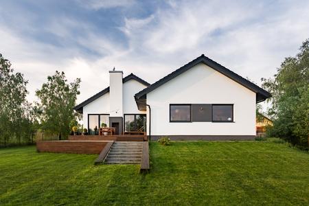 Élégante maison blanche avec jardin et terrasse, vue extérieure