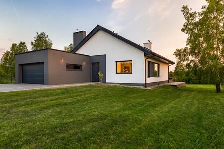 広い芝生、駐車場、屋外でスタイリッシュな家