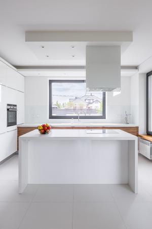 Elegante Cucina Bianca Con Isola, Cappa Aspirante E Finestra Foto ...