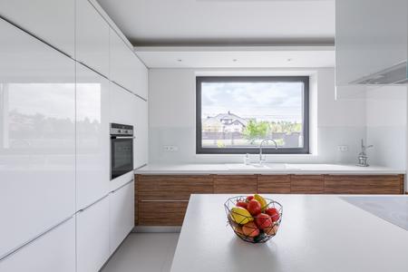 Modern design, white kitchen with island and big window Standard-Bild