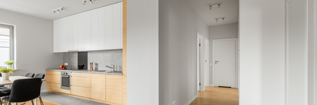 ceiling: White loft apartment with kitchen, wood floor panels and ceiling light, panorama Stock Photo
