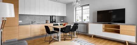 refrigerator: Modern open space kitchen, dining table and big television, panorama Stock Photo