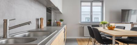 Stilvolle Küche mit Spülbecken im langen Countertop und Speiseraum in der modernen Wohnung, Panorama