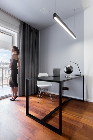 Woman standing in minimalistic home office with black table and white chair
