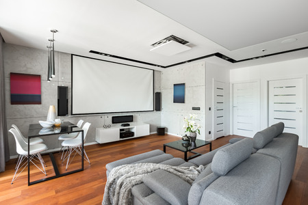 Modern Movie Room With Projector Screen, Gray Sofa, Black Table And White  Chairs Stock