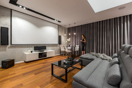 Woman in living room with projector screen, gray sofa and black coffee table Foto de archivo