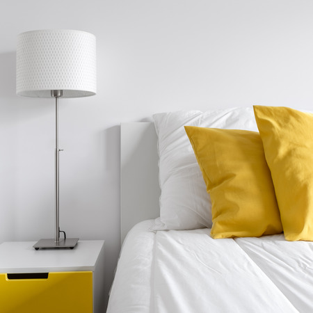 White bedroom with bed, lamp and modern, yellow side table