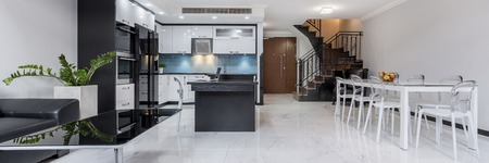 Modern, white, open plan apartment with gloss flooring, table, kitchen and staircase, panorama Stock Photo