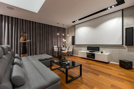 couch: Living room with projector screen, gray couch and black coffee table