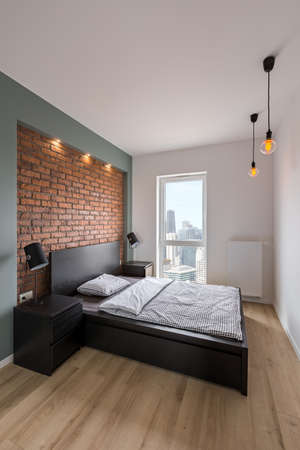 Loft bedroom with double bed and red, brick wall