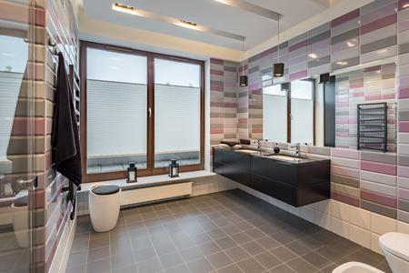 レンガ調タイル、黒のキャビネットと 2 つの流しの広々 としたバスルーム