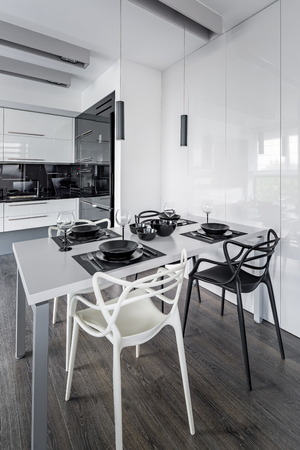 dining table and chairs: Home interior with white dining table, modern chairs and open kitchen