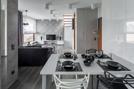 dining table and chairs: Modern apartment in gray and white with white dining table