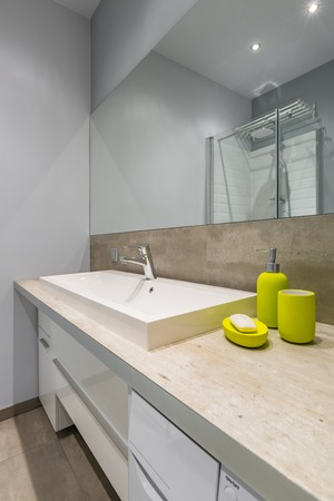 Modern bathroom with countertop basin, big mirror and green accessories Stock Photo