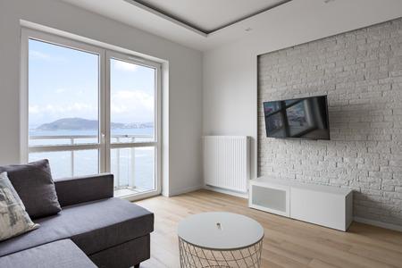 Stock Photo   Tv Living Room With Balcony, Gray Sofa And Decorative Brick  Wall