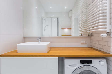 Bathroom with wooden countertop, mirror, shower and washer