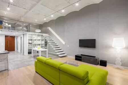 Interno di casa con divano verde, tv e soppalco Archivio Fotografico