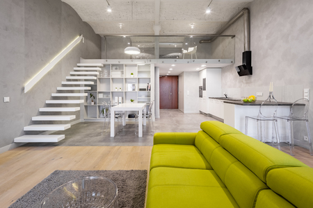 Storied loft apartment with green couch, carpet and transparent coffee table