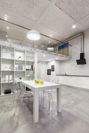 Interni in loft con tavolino bianco, sedie trasparenti e cucina aperta funzionale Archivio Fotografico