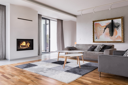 Modern living room with fireplace, sofa, balcony and pattern carpet Stockfoto