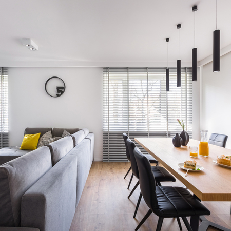 Modern home interior with communal table, black chairs and large sofa Banco de Imagens