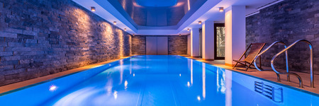Luxurious villa swimming pool with brick walls, evening view, panorama