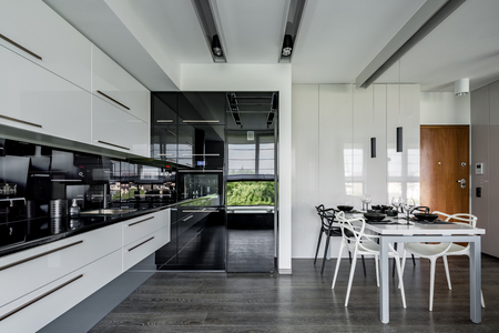 Contemporary kitchen in black and white with dining table Banco de Imagens