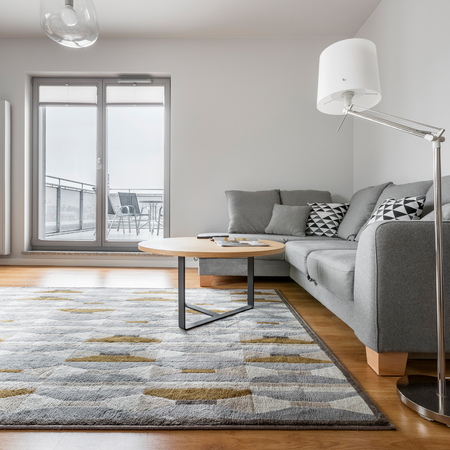 Grey and white living room with sofa, lamp, carpet, round table and balcony 스톡 콘텐츠