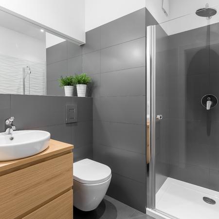 Bagno grigio elegante con grande doccia e mobili in legno