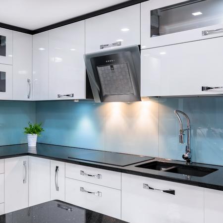Modern kitchen with white furniture and black worktop Reklamní fotografie