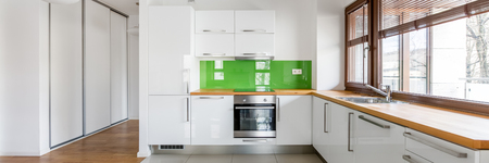 White, open kitchen with window, green backsplash and wooden countertop, panorama