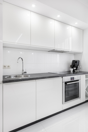 Stock Photo   White Modern Kitchenette Witch Steel Appliances And Granite  Countertop