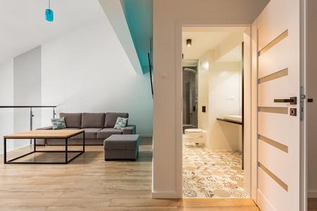 Camera con tavolo in legno, divano e porta aperta sul bagno