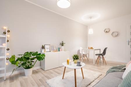 Biały salon w stylu skandynawskim z kanapą, stołem i szafką
