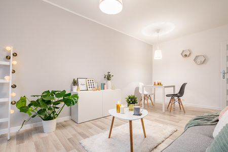 White living room in scandinavian style with couch, table and cabinet Foto de archivo