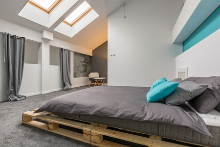 Simple attic bedroom with diy pallet bed and windows in ceiling