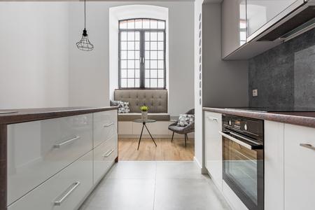 White kitchen with island and big, stylish window Stock fotó