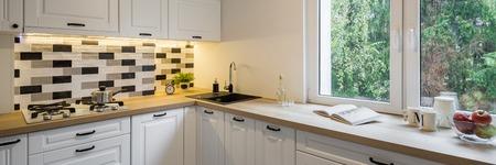 고전적인 흰색 캐비닛 및 창, 파노라마가있는 기능적인 주방
