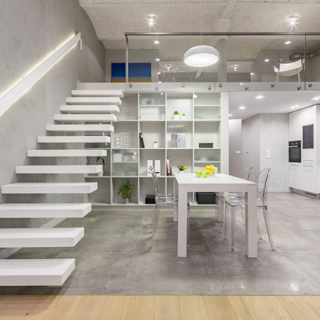 Appartamento mansardato con scala bianca a soppalco, tavolo, sedie e cucina a vista