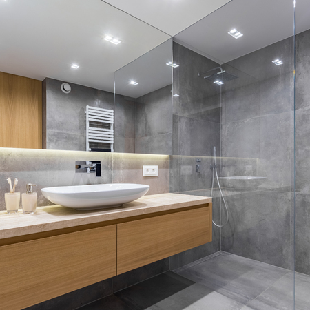 Gray bathroom with long countertop, mirror and walk in shower 版權商用圖片