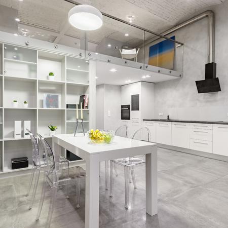Interni in loft con tavolino bianco, sedie trasparenti e cucina aperta funzionale
