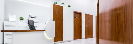 Panoramic view of modern reception in clinic with wooden doors and desk