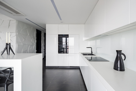 High gloss white kitchen with modern equipment and black flooring