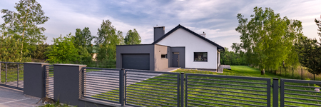 Exterior view of a house with fence and garage, panorama Imagens - 94578627