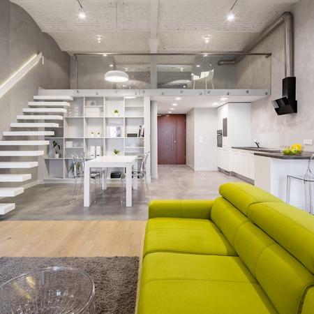 Loft a due piani con divano verde, moquette e tavolino trasparente