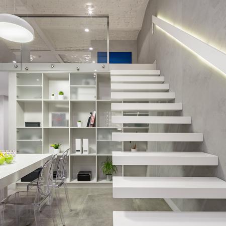 Appartamento a soppalco con scale bianche, moderne e soppalco con luce a led nella ringhiera